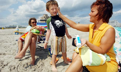 A mother applies sun cream to the face of a small child