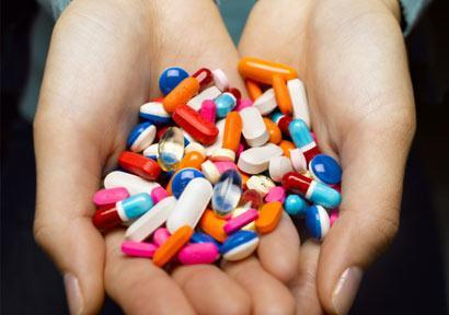 woman-holding-pills_410x290
